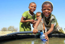 Bushman girls enjoy water from the well at Mothomelo